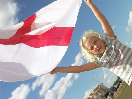 Girl playing with flag in a field on a sunny day