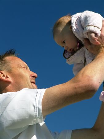 raises: Father holding baby in the air