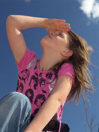 Young girl in jeans gazing upward, shielding eyes from the sun