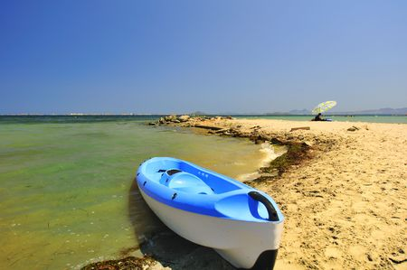 fibreglass: Blue and white kayak canoe at the waters edge.
