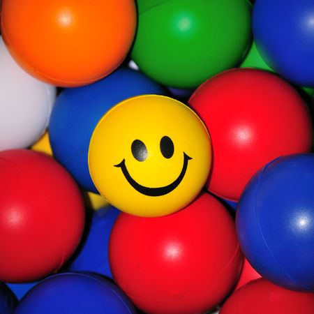 Smiling face amongst brightly colored balls photo