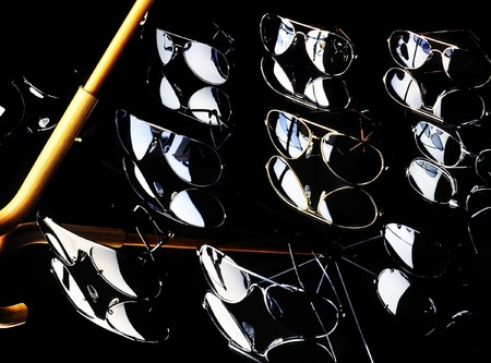 Studio shot of various aviator style sunglasses and reflections of a black umbrella. photo