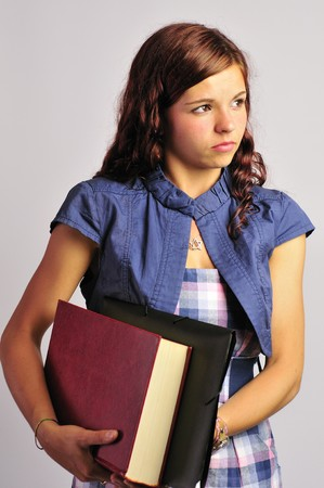 teenage girl dress: Pretty student girl carrying a folder and a large book