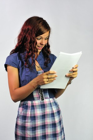 Happy, smiling girl reading a document photo