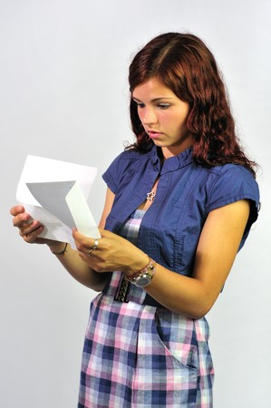 grades: Young woman reading a serious letter, report, bill etc.