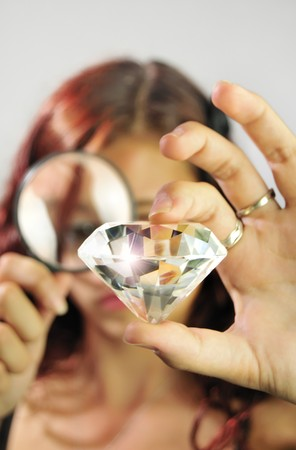 flaws: Young woman examines a diamond with a magnifying glass