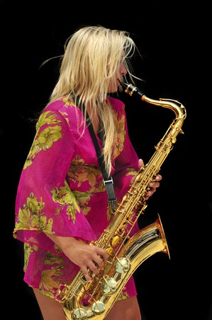 Girl in bright pink dress playing tenor sax.