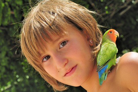Young girl with lovebird parrot on shoulder. Stock Photo