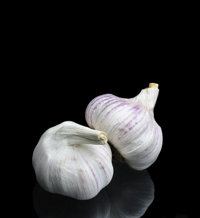 Two bulbs of garlic on black background.