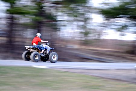 A youngster breaks the law as he rides the roadway on his four wheeler. Atleast he has his helmet on. Archivio Fotografico