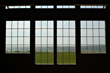 Looking out silhouetted windows over a lake front