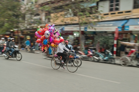 Women on a bicycle with colorful balloons on the street in Hanoi. Vietnam.