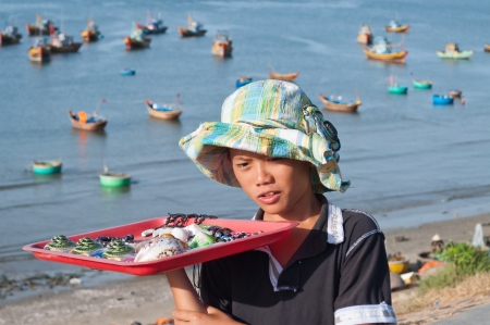 MUI NE, VIETNAM - DEC 21: Unidentified young seller in Fishing village on Dec 21, 2012, in Mui Ne, Vietnam. Mui Ne is a coastal resort town. Tourism has transformed Mui Ne into a resort destination since 1995. Stock Photo - 20263774