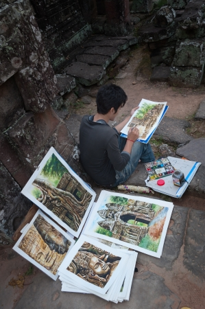SIEM REAP, CAMBODIA - DEC 26  Cambodian young artist paints a picture for sale to tourists at Banteay Kdei temple on Dec 26, 2012, in Siem Reap, Cambodia  Banteay Kdei is a Buddhist temple in Angkor