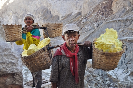 Worker carrying sulfur inside Ijen crater on December 3, 2011   Workers pick up the 60-90 kg basket with the sulfur  The work is low-paid and very onerous   Editorial