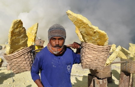condensation basket:  Worker carrying sulfur inside Ijen crater on December 3, 2011   Workers pick up the 60-90 kg basket with the sulfur  The work is low-paid and very onerous