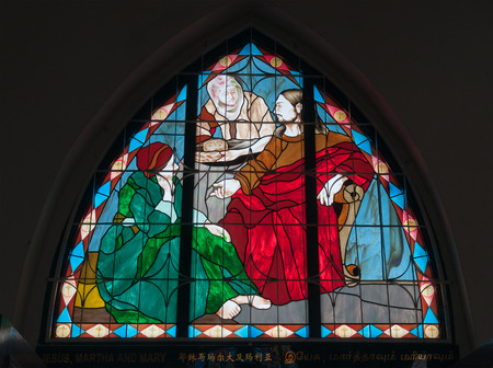 MALACCA, MALAYSIA - DEC 20, 2013: Stained Glass Window Jesus, Martha and Mary of Church of St. Francis Xavier. Malacca City is the capital city of the Malaysian state of Malacca.
