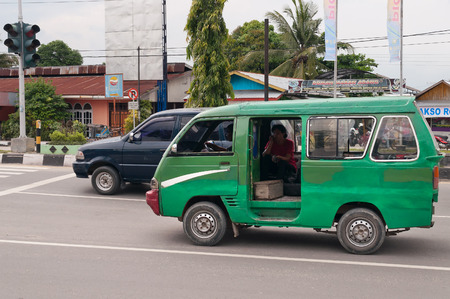 internationally: DUMAI, INDONESIA - DEC 21, 2013: Public transport on the street in Dumai.  Dumai is an important transport and trade centre, both regionally and internationally