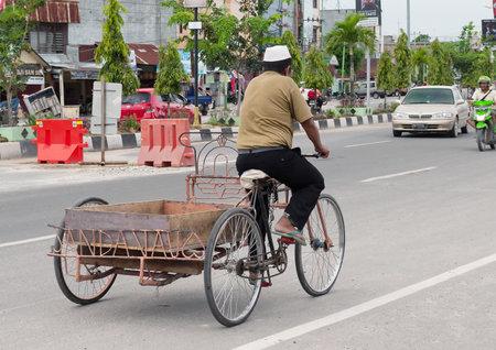 regionally: DUMAI, INDONESIA - DEC 21, 2013: Transport on the street.  Dumai is an important transport and trade centre, both regionally and internationally