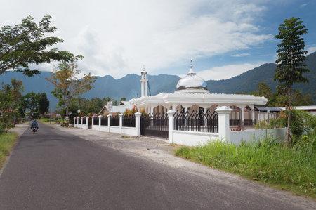 Bukittinggi,印度尼西亚 -  2013年12月24日:清真寺在湖Maninjau湖。Maninjau湖(Danau Maninjau)是西苏门答腊湖的一个火山岛湖。它的面积为99.5公里