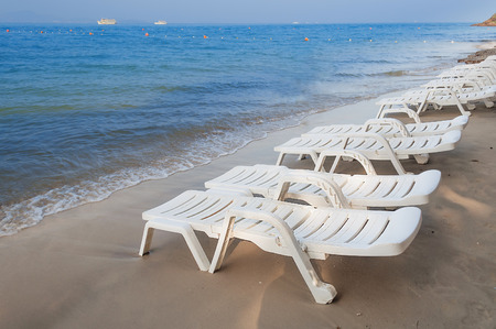 loungers: White sun loungers on the beach.