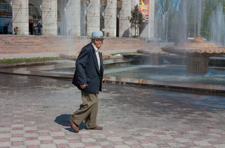 kyrgyz republic: BISHKEK, KYRGYZSTAN - MAY 02, 2014: Elderly asian man walking on Ala-Too Square. Bishkek formerly  Frunze, is the capital and the largest city of the Kyrgyz Republic.  The population - 900,000 people Editorial