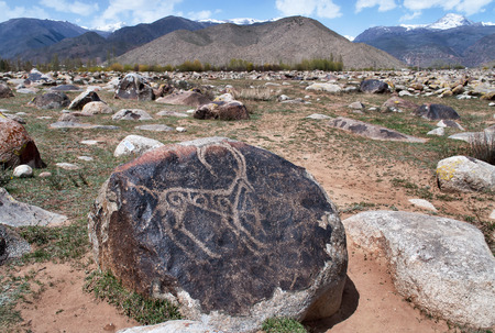 Ancient petroglyph on the stone. Dating from 8 th c BC - 5 th c. AN and located in Cholpon Ata, Issyk-Kul, Kyrgyzstan Imagens