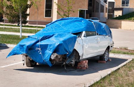 tarpaulin: ASTANA, KAZAKHSTAN - MAY 10, 2014: Broken car without wheels stands on bricks covered by blue tarpaulin