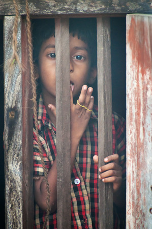 kovalam: KOVALAM, INDIA, DEC 28, 2014: Unidentified Indian boy looks through a window at home in small fishing village