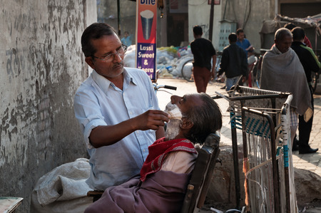 AMRITSAR, INDIA, DEC - 6, 2014: An unidentified street barber shaving a man on the street. A lot of Indian poor people shave with a straight razor on the streets in India
