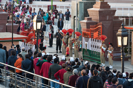happens: AMRITSAR, INDIA, DEC - 6, 2014: The India-Pakistan Wagah Border Closing Ceremony. It happens at the border gate, two hours before sunset each day. The flag ceremony is conducted by Indian Border Security Force and Pakistan Rangers.