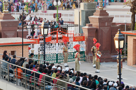 wagah: AMRITSAR, INDIA, DEC - 6, 2014: The India-Pakistan Wagah Border Closing Ceremony. It happens at the border gate, two hours before sunset each day. The flag ceremony is conducted by Indian Border Security Force and Pakistan Rangers.