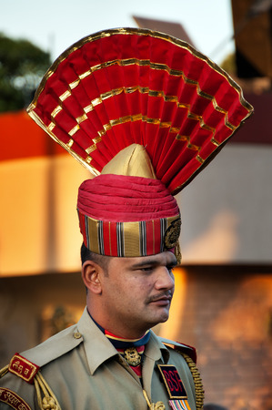 happens: AMRITSAR, INDIA, DEC - 6, 2014: Unidentified Indian guard in the India-Pakistan Wagah Border Closing Ceremony. The flag ceremony happens at the border gate, two hours before sunset each day.