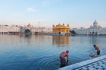 darbar sahib: AMRITSAR, INDIA, DEC - 7, 2014: Unidentified Sikh men  bath in the holy lake at Golden Temple (Harmandir Sahib also Darbar Sahib) in the early morning. Golden Temple is the holiest Sikh gurdwara located in the city of Amritsar, Punjab, India.