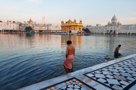 harmandir sahib: AMRITSAR, INDIA, DEC - 7, 2014: Unidentified Sikh men  bath in the holy lake at Golden Temple (Harmandir Sahib also Darbar Sahib) in the early morning. Golden Temple is the holiest Sikh gurdwara located in the city of Amritsar, Punjab, India.
