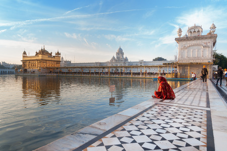 harmandir sahib: AMRITSAR, INDIA, DEC - 7, 2014: Unidentified woman in a red saree sits and pray in Golden Temple (Harmandir Sahib also Darbar Sahib) in the early morning. Golden Temple is the holiest Sikh gurdwara located in the city of Amritsar, Punjab, India.