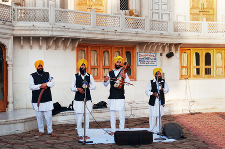 gurudwara: AMRITSAR, INDIA, DEC - 7, 2014: Indian musicians playing local instruments at Golden Temple (Harmandir Sahib also Darbar Sahib). Golden Temple is the holiest Sikh gurdwara located in the city of Amritsar, Punjab, India. Editorial