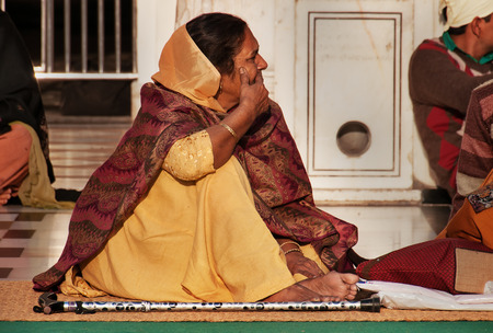 darbar sahib: AMRITSAR, INDIA, DEC - 7, 2014: Unidentified woman in beige saree  in Golden Temple (Harmandir Sahib also Darbar Sahib). Golden Temple is the holiest Sikh gurdwara located in the city of Amritsar, Punjab, India.