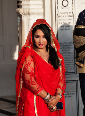 darbar sahib: AMRITSAR, INDIA, DEC - 7, 2014: Unidentified woman in a red saree  in Golden Temple (Harmandir Sahib also Darbar Sahib). Golden Temple is the holiest Sikh gurdwara located in the city of Amritsar, Punjab, India. Editorial