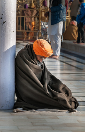 AMRITSAR, INDIA, DEC - 7, 2014: Unidentified Sikh man praying in Golden Temple (Harmandir Sahib also Darbar Sahib). Golden Temple is the holiest Sikh gurdwara located in the city of Amritsar, Punjab, India.