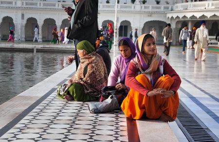 darbar: Amritsar, India, dicembre - 7, 2014: le donne indiane non identificati seduto vicino al lago a Golden Temple (Harmandir Sahib anche Darbar Sahib). Golden Temple � il pi� sacro Sikh Gurdwara situato nella citt� di Amritsar, Punjab, India.