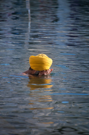 darbar: Amritsar, India, dicembre - 7, 2014: non identificato uomo Sikh in preghiera nella santa lago a Golden Temple (Harmandir Sahib anche Darbar Sahib). Golden Temple � il pi� sacro Sikh Gurdwara situato nella citt� di Amritsar, Punjab, India. Editoriali