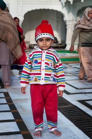 darbar sahib: AMRITSAR, INDIA, DEC - 7, 2014: Unidentified child in Golden Temple (Harmandir Sahib also Darbar Sahib). Golden Temple is the holiest Sikh gurdwara located in the city of Amritsar, Punjab, India. Stock Photo