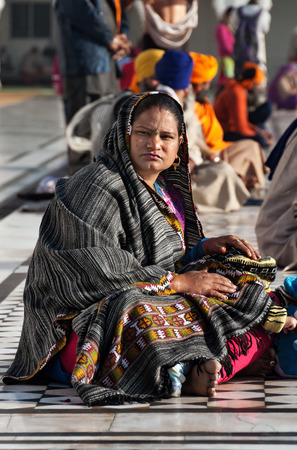 AMRITSAR, INDIA, DEC - 7, 2014: Unidentified Indian woman with child sitting near the lake at Golden Temple (Harmandir Sahib also Darbar Sahib). Golden Temple is the holiest Sikh gurdwara located in the city of Amritsar, Punjab, India. Stock Photo