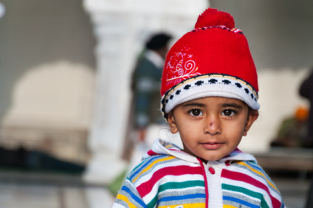 harmandir sahib: AMRITSAR, INDIA, DEC - 7, 2014: Unidentified child in Golden Temple (Harmandir Sahib also Darbar Sahib). Golden Temple is the holiest Sikh gurdwara located in the city of Amritsar, Punjab, India. Stock Photo