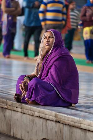 gurdwara: AMRITSAR, INDIA, DEC - 7, 2014: Unidentified Indian women in purple sari sitting near the lake at Golden Temple (Harmandir Sahib also Darbar Sahib). Golden Temple is the holiest Sikh gurdwara located in the city of Amritsar, Punjab, India. Stock Photo