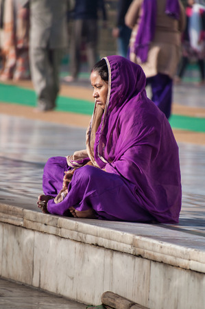 harmandir sahib: AMRITSAR, INDIA, DEC - 7, 2014: Unidentified Indian women in purple sari sitting near the lake at Golden Temple (Harmandir Sahib also Darbar Sahib). Golden Temple is the holiest Sikh gurdwara located in the city of Amritsar, Punjab, India. Stock Photo