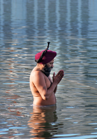 harmandir sahib: AMRITSAR, INDIA, DEC - 7, 2014: Unidentified Sikh man praying in the holy lake at Golden Temple (Harmandir Sahib also Darbar Sahib). Golden Temple is the holiest Sikh gurdwara located in the city of Amritsar, Punjab, India.