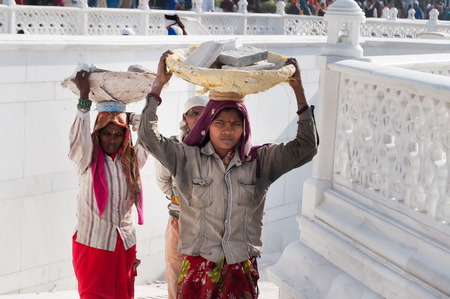gurdwara: AMRITSAR, INDIA, DEC - 7, 2014: Unidentified women carry basket of stones on their head at Golden Temple (Harmandir Sahib also Darbar Sahib). Golden Temple is the holiest Sikh gurdwara located in the city of Amritsar, Punjab, India.