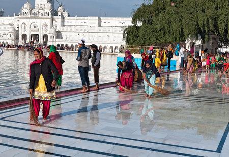 darbar: Amritsar, India, dicembre - 7, 2014: non identificato le donne indiane pavimento pulito vicino Tempio d'oro prima della preghiera della sera. Harmandir Sahib anche Darbar Sahib � il pi� sacro Sikh Gurdwara situato nella citt� di Amritsar, Punjab, India.